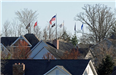 Closer View of Flags Raised Above a Residential Area